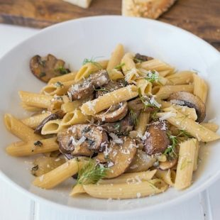 Dinner is served pasta, mushrooms, fennel and sage in a white bowl