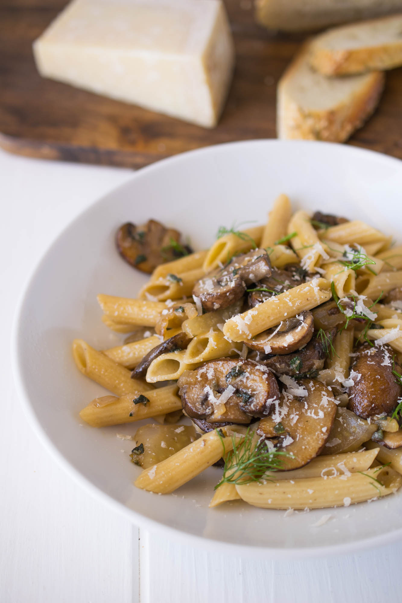Easy mushroom, fennel & sage pasta in a white bowl with crusty bread and Parmesan cheese