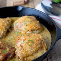 A cast iron skillet cooking up 4 chicken thighs in a Dijon sauce