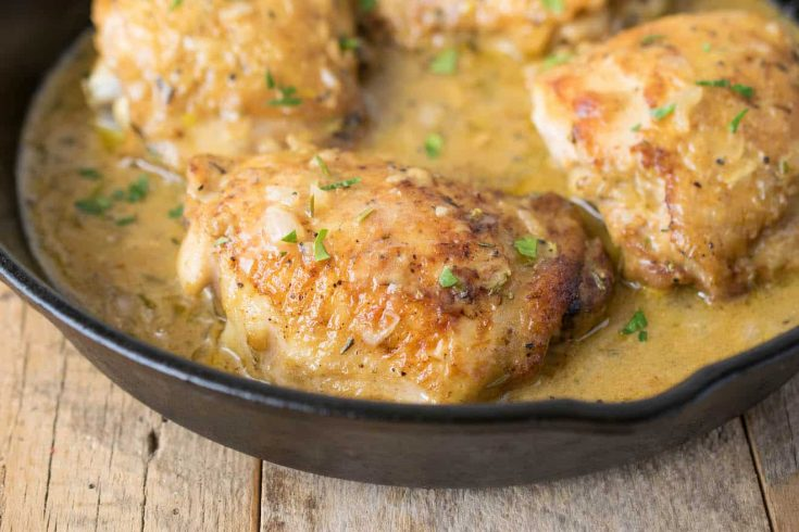 A closeup of a browned chicken thigh in a cast iron pan bathed in Dijon sauce