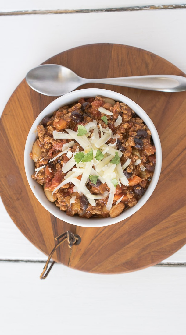 The bowl of chili from overhead on a round wood board with a spoon