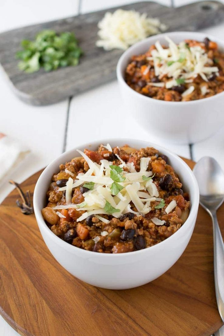 Turkey chili in a white bowl topped with grated cheese and cilantro