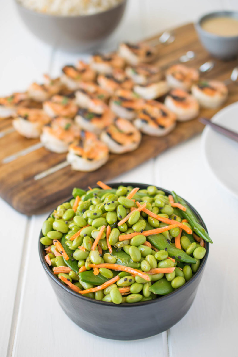 Edamame and snap peas in a black bowl with grilled shrimp