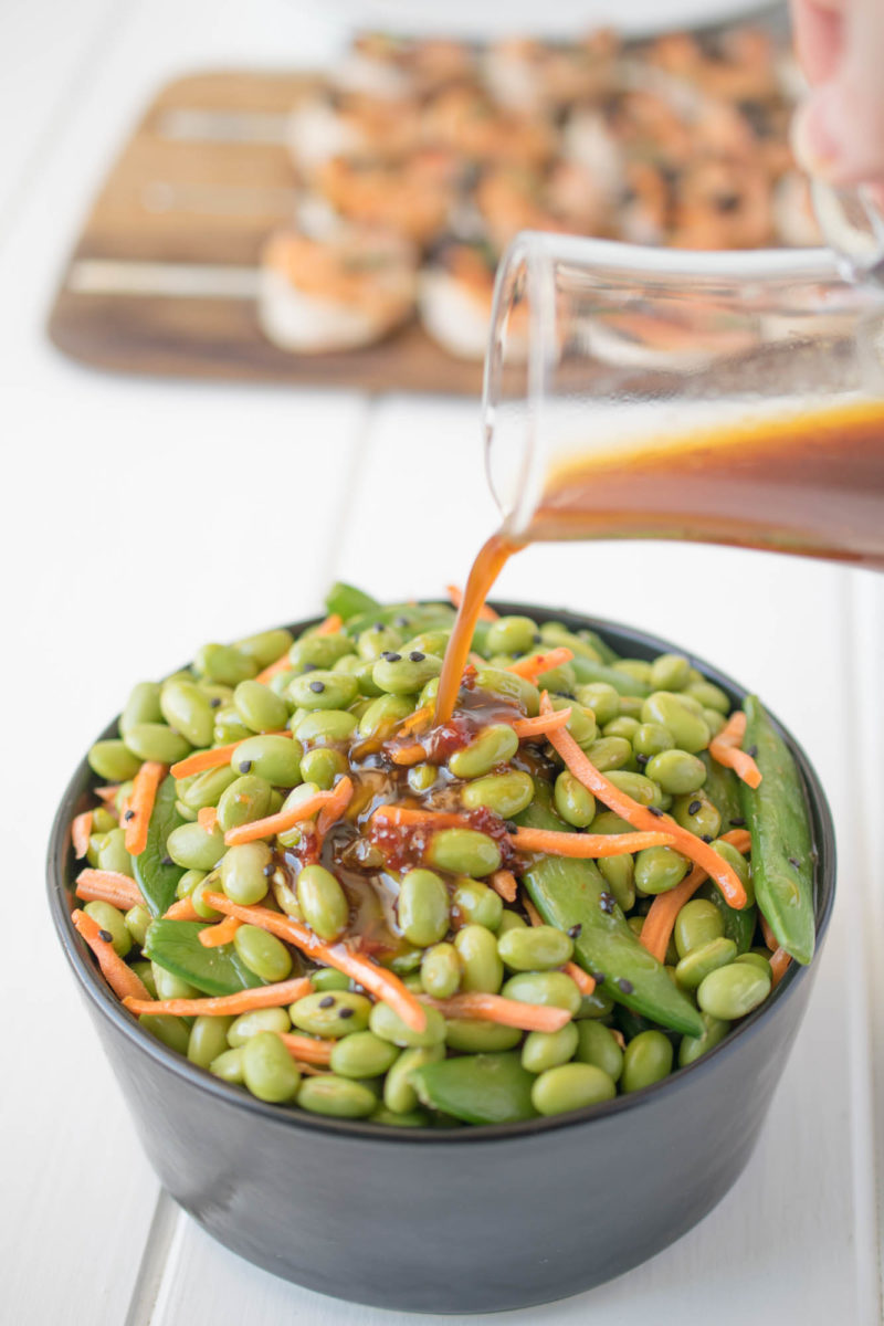 Pouring sesame ginger dressing onto a bowl of edamame and snap peas