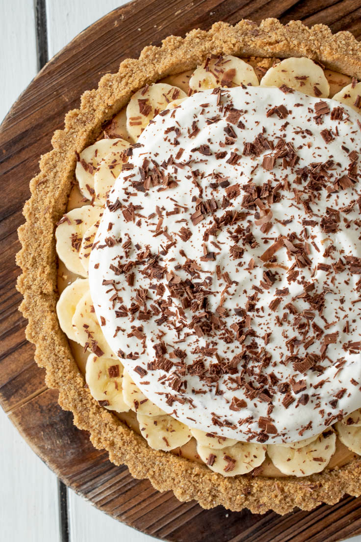 A closeup of the pie showing the slices of banana, whipped cream and shaved chocolate