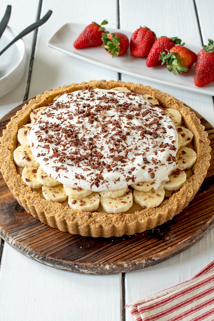 Banoffee pie with a graham cracker crust, toffee, sliced bananas, whipped cream and shaved chocolate served with fresh strawberrie