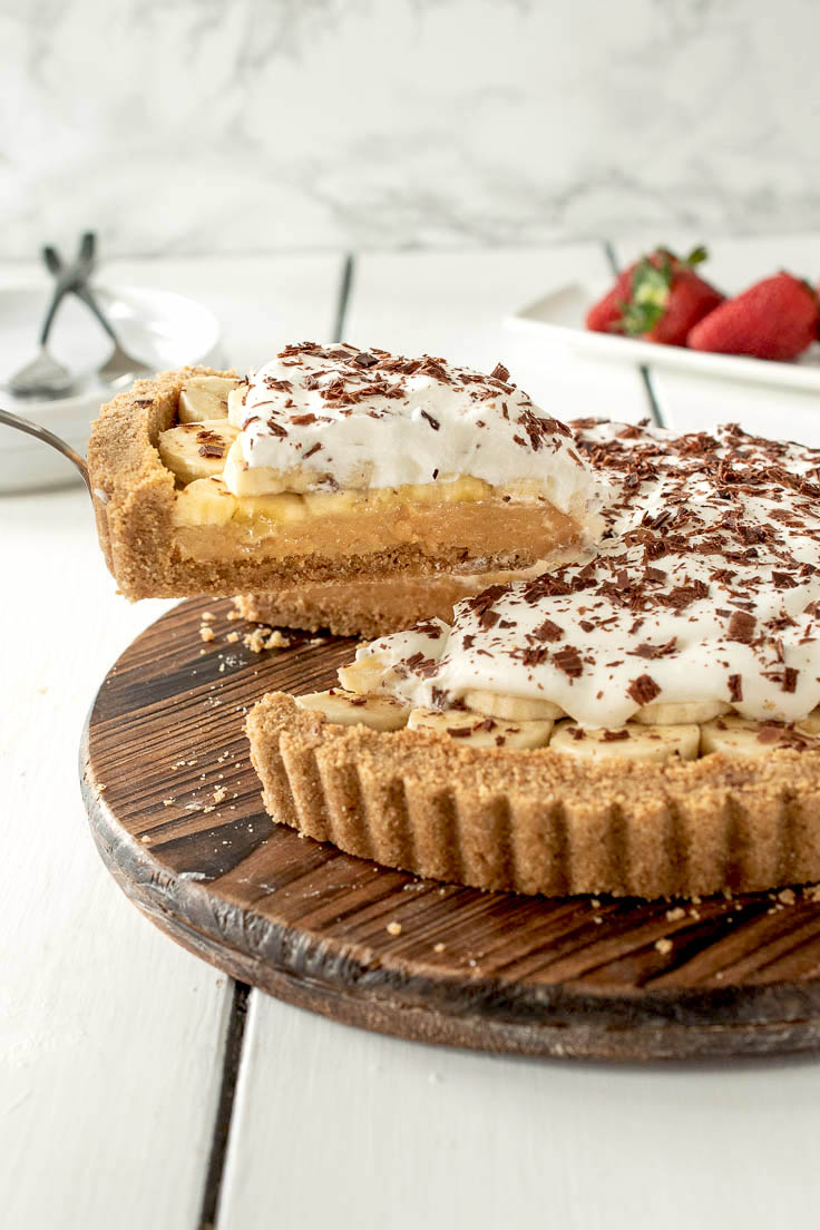 A slice of Banoffee pie on a cake server showing the layers of crust, toffee, banana and cream