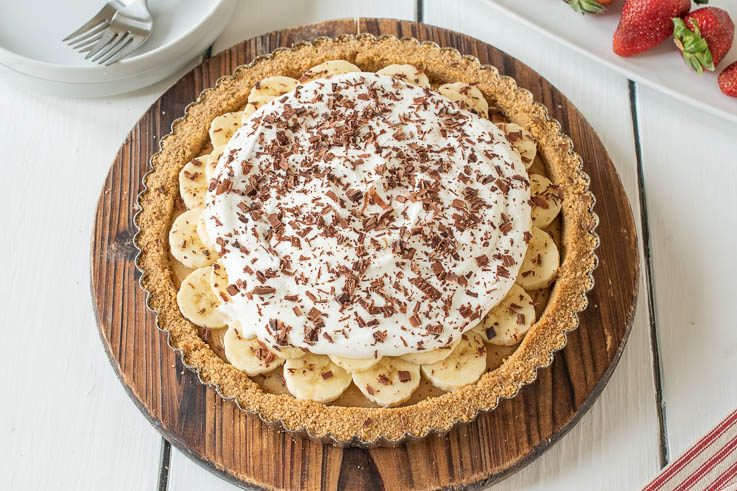 Banoffee pie on a round wood board with fresh strawberries