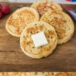 English crumpets on a wood board with melting butter