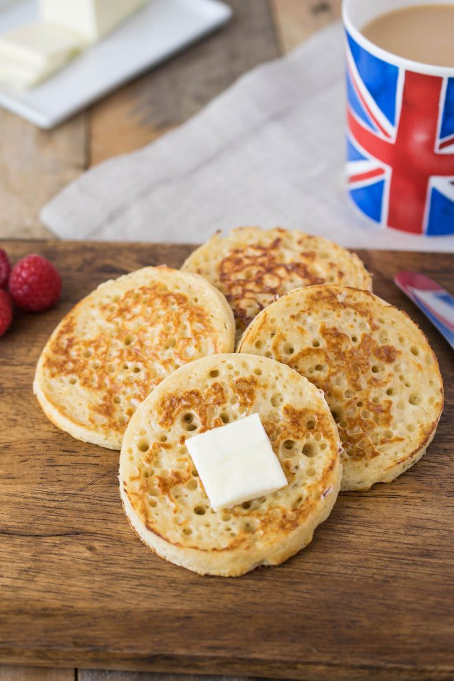 Browned English crumpets topped with creamy butter