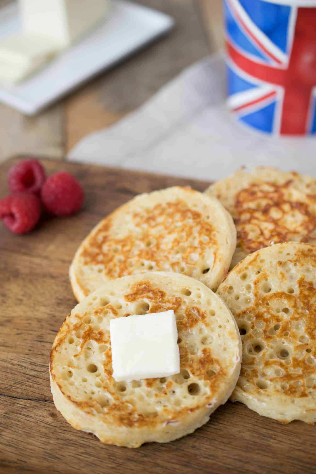 English crumpets lined up on a board topped with butter