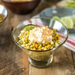 Esquites Mexican Street Corn Salad in a glass bowl with fresh limes