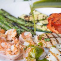Pouring herb sauce over grilled shrimp, chicken and vegetables on a white platter