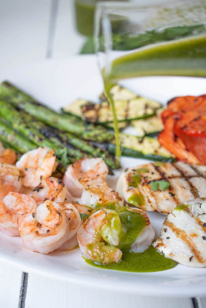 Pouring sauce over grilled shrimp, chicken and vegetables on a white platter