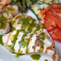 2 grilled chicken breasts topped with herb sauce