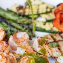 A plate of grilled shrimp and vegetables being drizzled with herb sauce