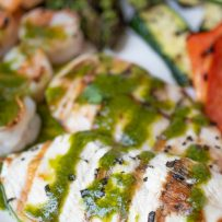 Perfectly grilled chicken breast drizzled with herb sauce