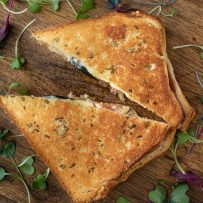 Fig and prosciutto grilled cheese cut in half garnished with micro greens
