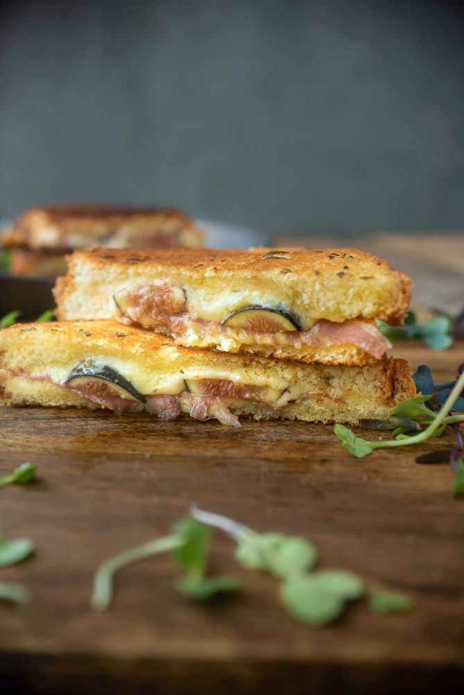 Fresh figs and prosciutto in a grilled cheese shown from the side showing the filling