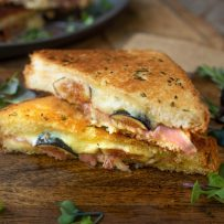 Cheese and fresh fig oozing out of a half of grilled cheese