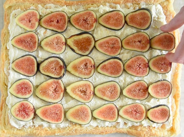 Fresh fig slices are arranged on top of the ricotta and tart