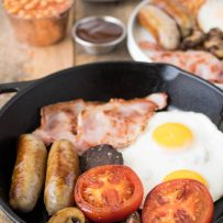 Sausages, tomato, mushrooms, bacon and egg in a cast iron skillet