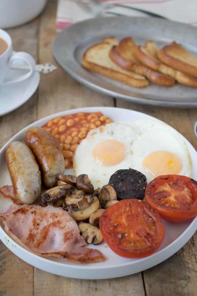 A large white plate with fried eggs, baked beans, sausages, mushrooms, bacon, tomatoes and black pudding.