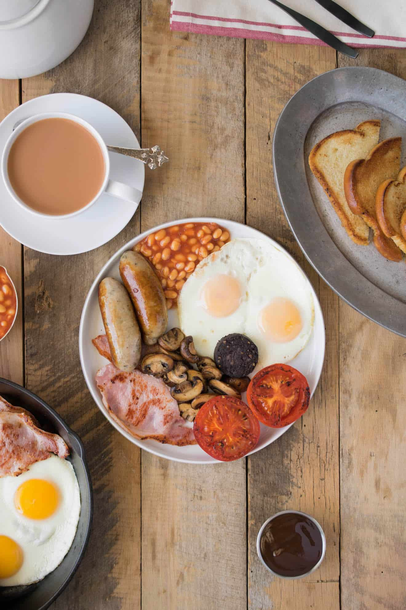 A Full English breakfast on a white plate with fried break and a cup of tea