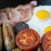 A closeup of a browned tomato with mushrooms, sausage, bacon and eggs