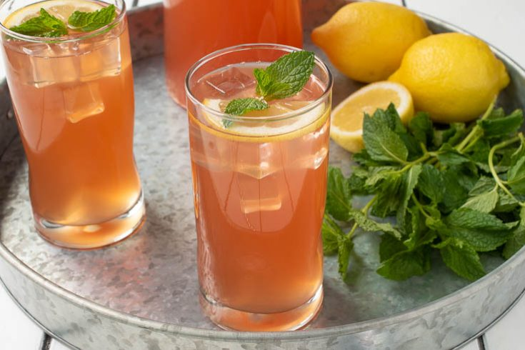 Ginger mint lemonade in a glass garnished with lemon and fresh mint