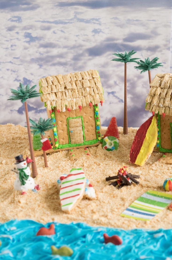 An edible beach scene made from graham crackers and frosting with cookie surfboards