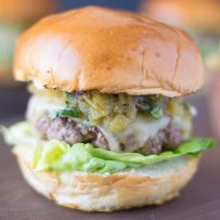 The burger from the side showing the melted cheese, chiles and lettuce