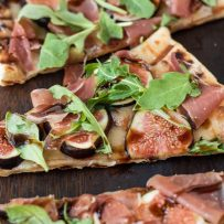 A slice of grilled flatbread topped with fontina, sliced fresh figs, prosciutto, arugula leaves and balsamic glaze
