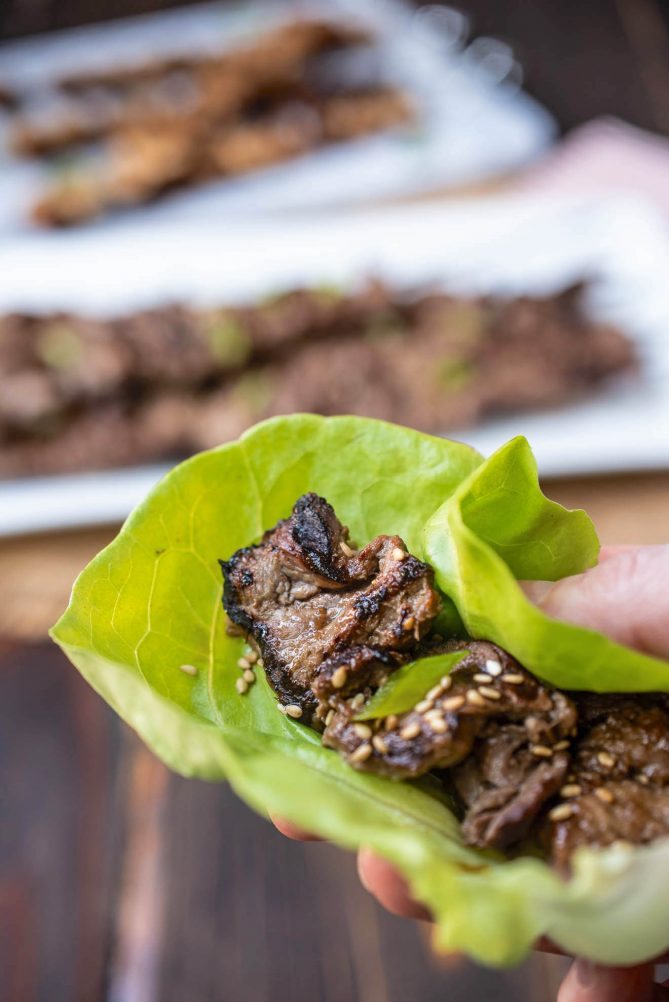 Pieces of grilled beef inside a lettuce leaf with sesame seeds and sliced scallion
