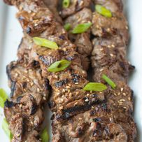 Perfectly grilled beef on skewers lined up on a white plate