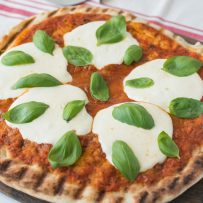 Grilled pizza with sauce, fresh mozzarella and green basil leaves
