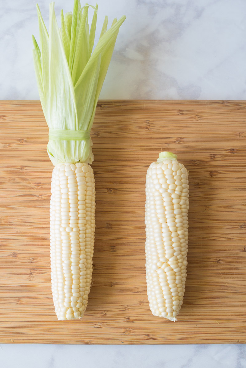 2 ears of corn. One with the husks attached, one with them removed