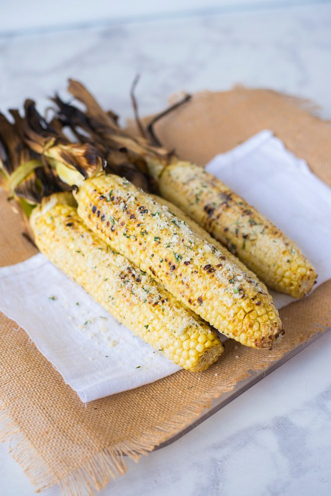 Grilled corn cobs coated with butter, garlic, Parmesan cheese and basil