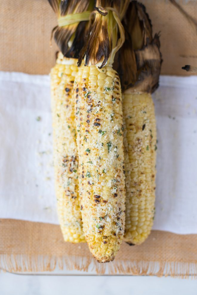 3 corn cobs that are grilled and covered with cheese, garlic and herbs