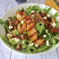 Green arugula, grilled pears and crisp proscuitto salad in a white bowl