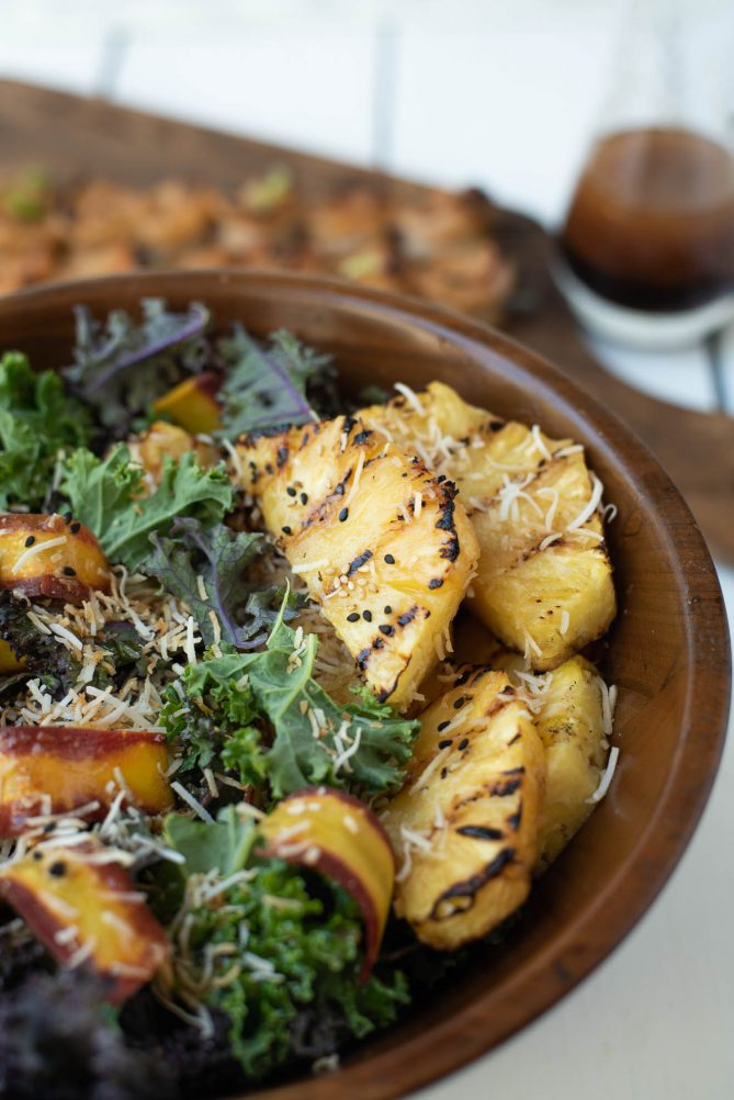 A wood bowl of green and red kale topped with grilled pineapple, shaved carrots and toasted coconut