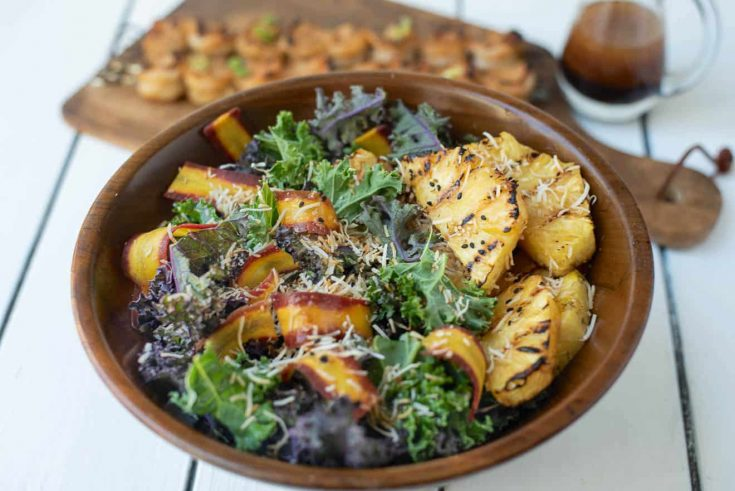 Slices of grilled pineapple on a bed of kale with shaved carrot and toasted coconut