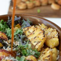 Pineapple with grill marks in a kale salad with salad dressing being poured
