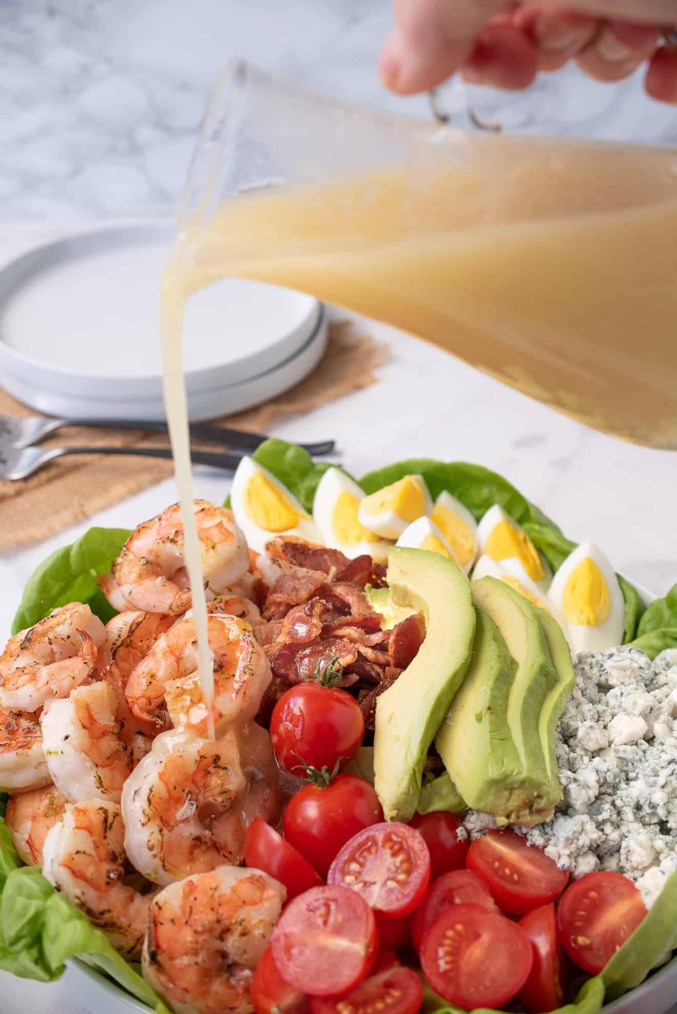 Pouring salad dressing over a grilled shrimp cobb salad