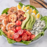 Grilled shrimp, tomato, bacon, avocado, egg and blue cheese on top of lettuce make up this grilled shrimp cobb salad