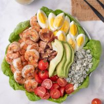 A large platter with lettuce leaves, grilled shrimp, tomato, bacon, egg, avocado and blue cheese