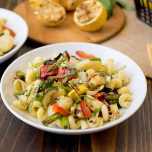 A white bowl of grilled spring vegetable pasta salad