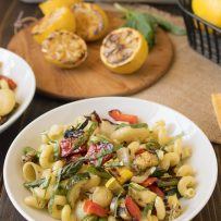 Grilled spring vegetables mixed with pasta and lemon dressing in a white bowl with grilled lemons in the background