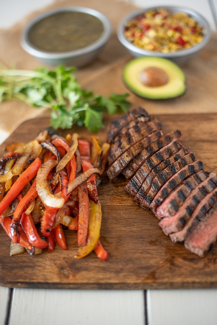 Sliced, grilled steak and grilled peppers and onions on a board with avocado and salsa ready to build the bowl