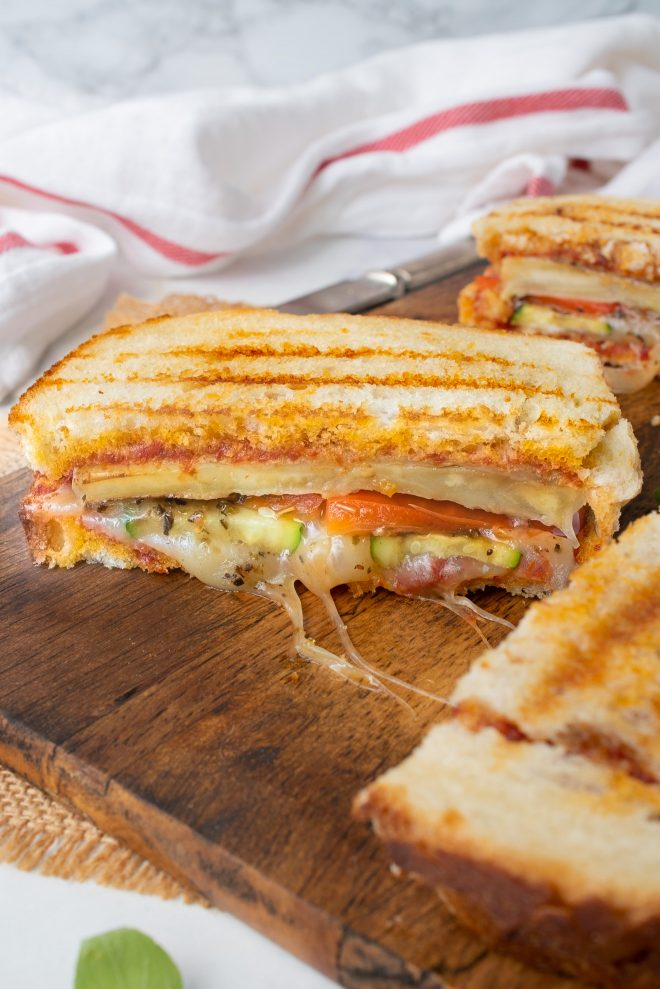 Grilled summer vegetable panini on a cutting board cut in half